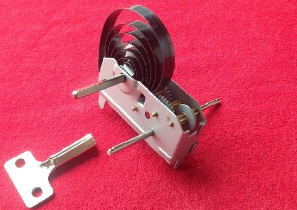 A New replacement spring winding drive motor unit with key.